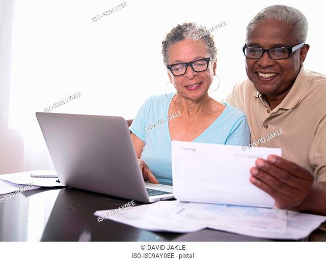 Senior couple sitting at table, using laptop, looking at paperwork