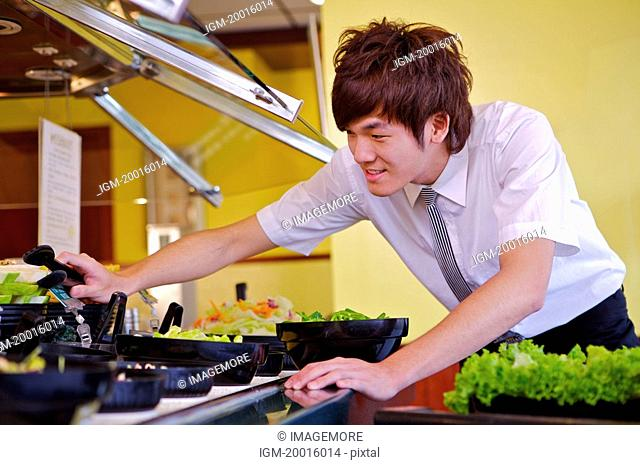 Young waiter preparing for the food in the restaurant,Restaurant