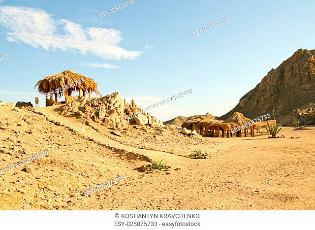 Traditional rural African reed and thatch hut and mountain landscape on the background