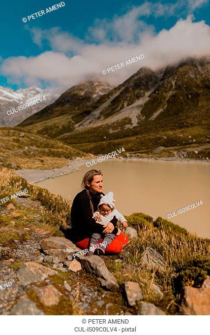 Mother with baby enjoying scenic view by lake, Wanaka, Taranaki, New Zealand