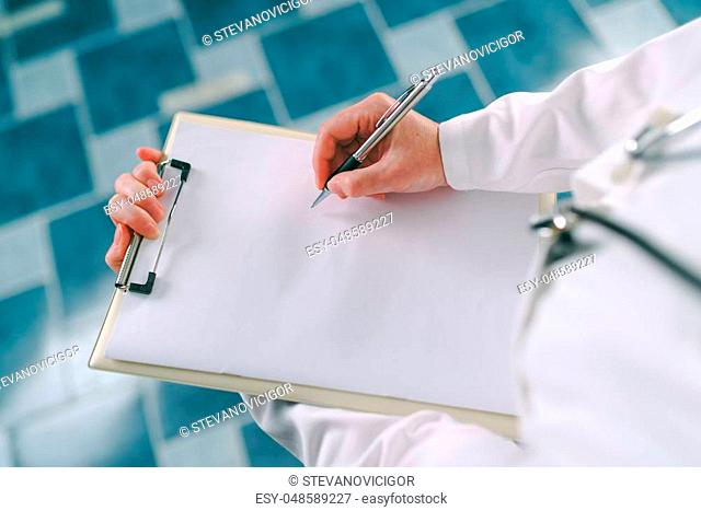 Female doctor in white uniform writing on clipboard paper patient's medical history or medicine prescription