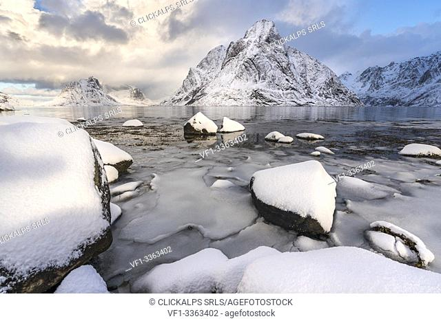 Olstinden peak in winter, with ice and snow on the rocky beach in the foreground. Reine, Nordland county, Northern Norway region, Norway