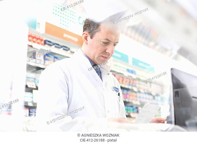 Pharmacist reviewing prescription at computer in pharmacy
