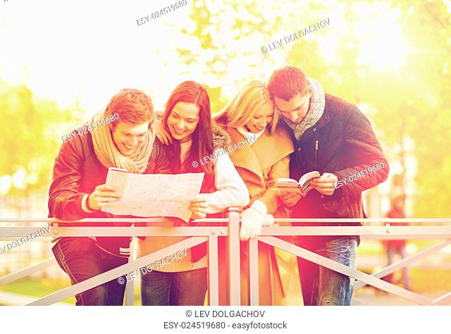 holidays and tourism concept - group of friends or couples with tourist map in autumn park
