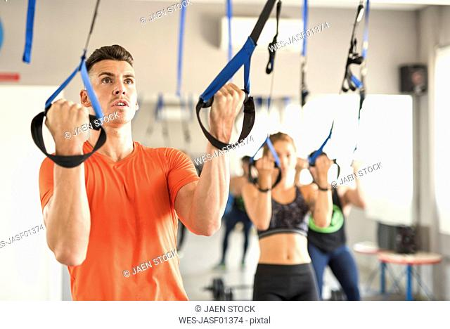 People doing suspension training in gym