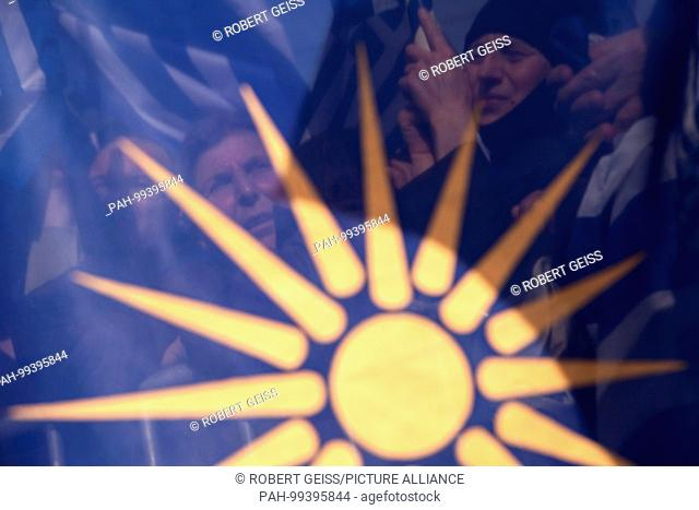 "Greek women behind flag of Greek region Makedonia with """"Star of Vergina Sun"""",during rally over FYROM-s official name, objects to Macedonia's name because..."