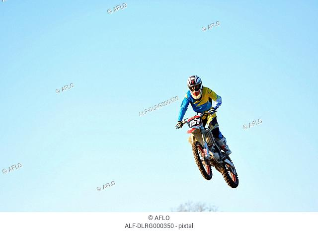 Motocross biker jumping over dirt track