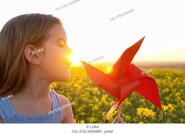 Girl playing with pinwheel outdoors