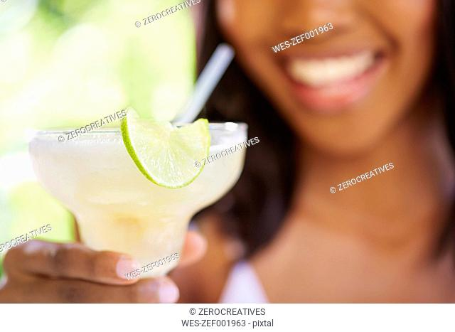 Woman's hand holding cocktail glass decorated with slice of lime