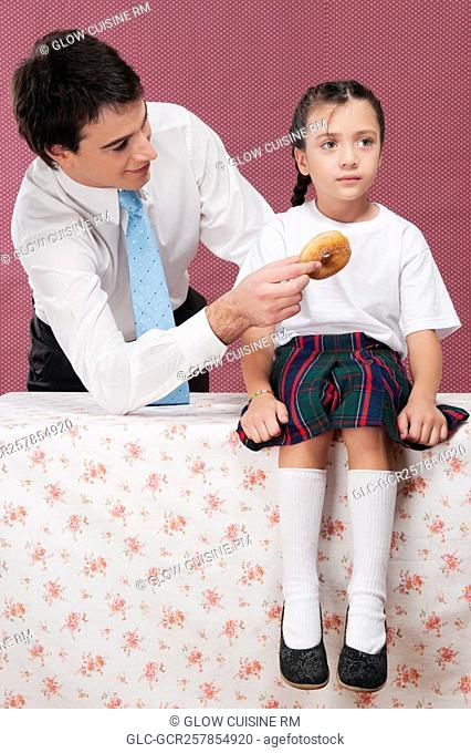 Man feeding donut to his daughter