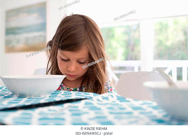 Girl at dining table looking down