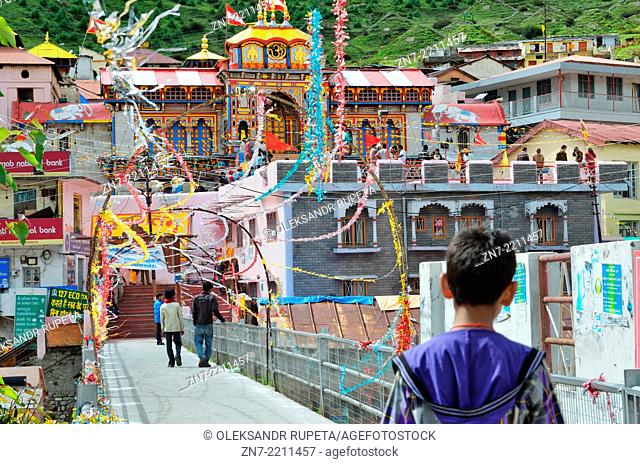 Pilgrims walking on a bridge to the Badrinath temple in the Himalayas, India
