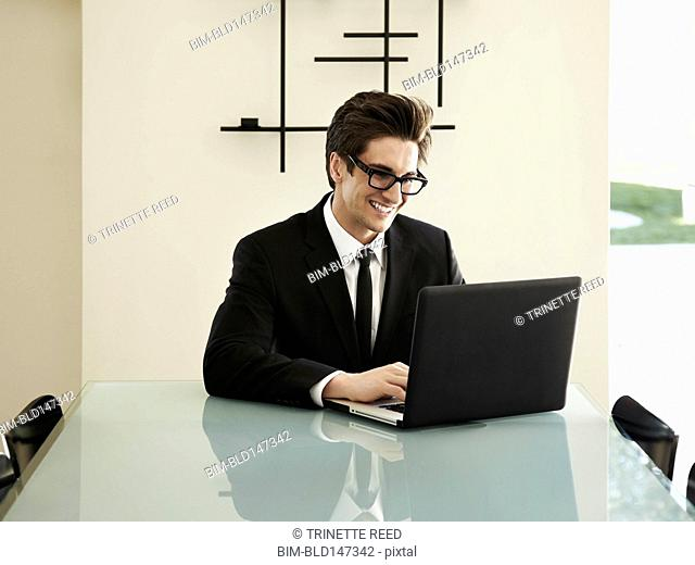 Trendy Caucasian businessman sitting at conference table typing on laptop