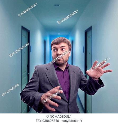 Scared businessman in the dark corridor