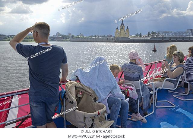 Local people on a ferry boat on the Volga river with views of the Alexander Nevsky Cathedral and 2018 World Cup football stadium in Nizhny Novgorod, Russia