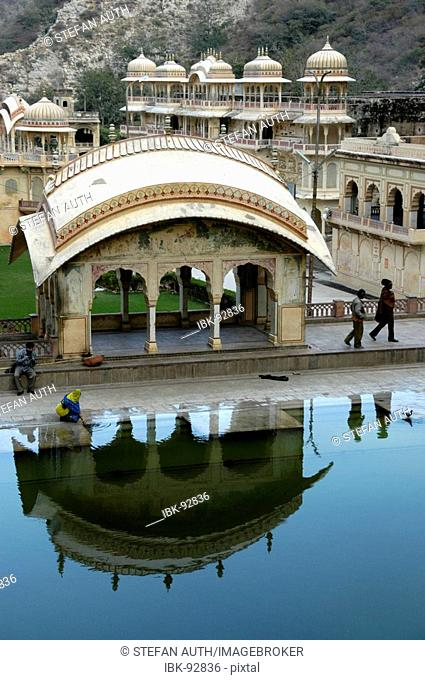 Hindu temple reflect in a water pond Galta canyon Jaipur Rajasthan India