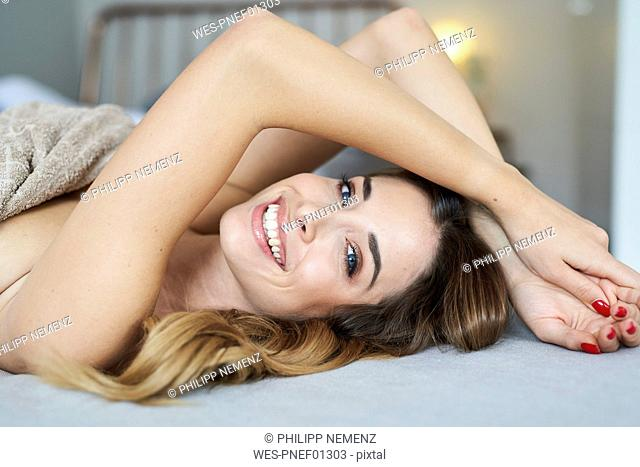 Portrait of happy young woman lying in bed