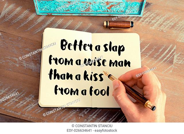 Retro effect and toned image of a woman hand writing on a notebook. Handwritten quote Better a slap from a wise man than a kiss from a fool as inspirational...
