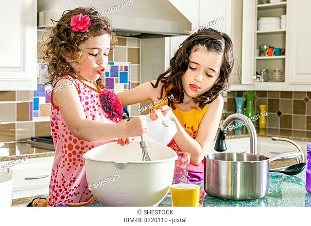 Sisters baking in kitchen