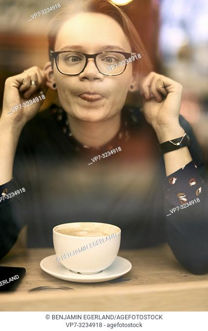 defiant woman behind glass window in café pulling by her ears and protruding tongue, Munich, Germany