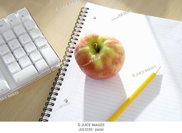 Apple, notepad and pencil on office desk, close-up, elevated view still life
