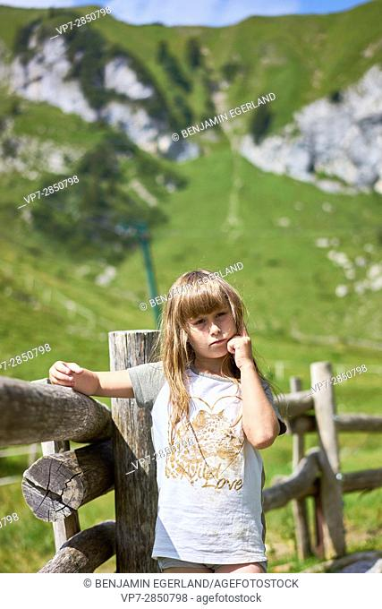 Thoughtful and confident female child standing in the nature of Bavarian mountains