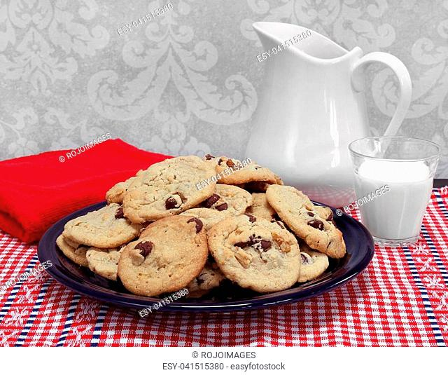 A large plate of homemade chocolate chip and walnut cookies with a pitcher and a glass of milk