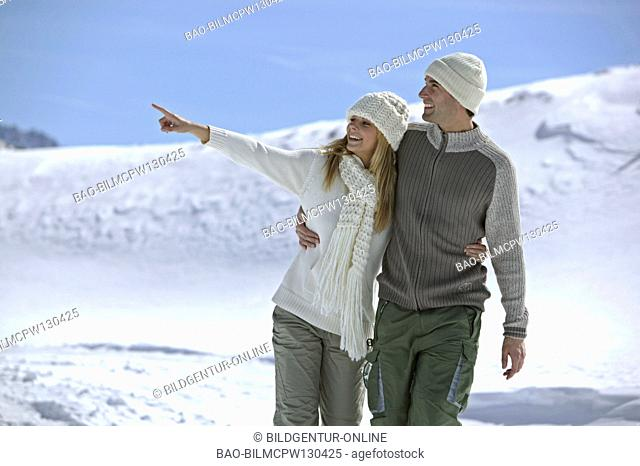 young couple walking in winter landscape
