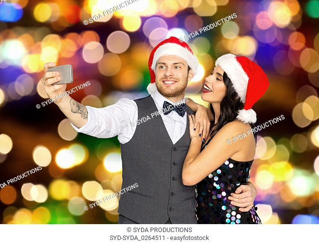 couple in santa hats taking selfie at christmas