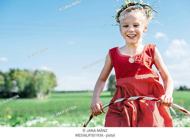 Happy girl with hula hoop wearing flower wreath