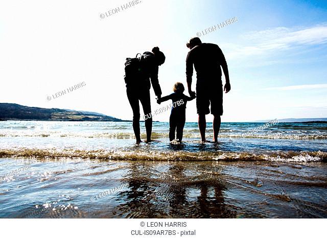 Family holding hands on beach, Loch Eishort, Isle of Skye, Hebrides, Scotland