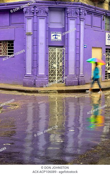 Street photography in central Havana- Reflections in the wet pavement of Calle Neptuno on a rainy day