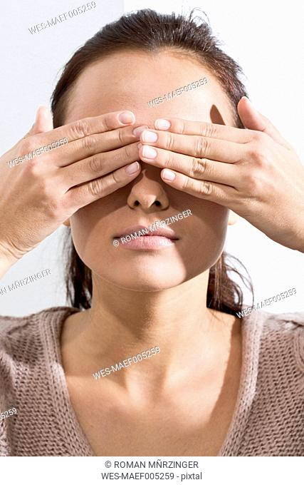 Portrait of young woman covering eyes