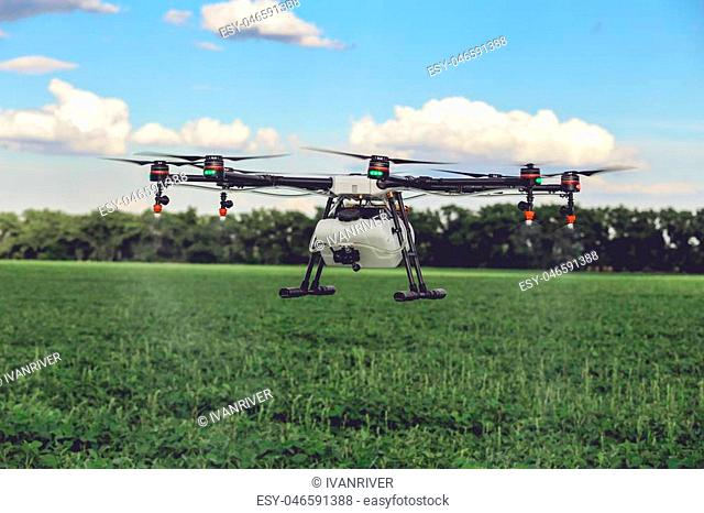 Professional large drone spray water over a green field. Agriculture industry concept drone with flying green field
