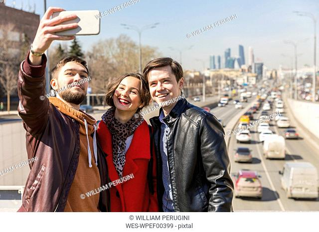 Russia, Moscow, friends taking a selfie in the city, road in the background