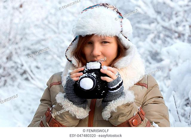 Beautiful young woman in down jacket, fingerless mittens and hat with white fur looking sly and holding knitted camera at the background of snowy forest