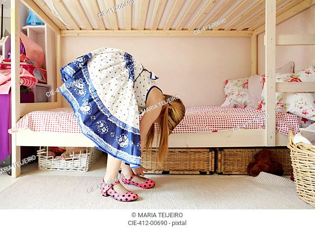 Girl in dress bending over and putting on polka-dot shoes in bedroom