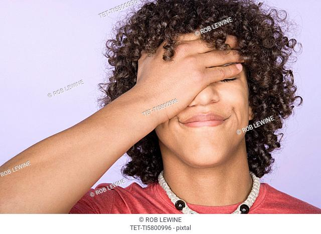 Portrait of teenage boy 14-15 covering eyes with hand