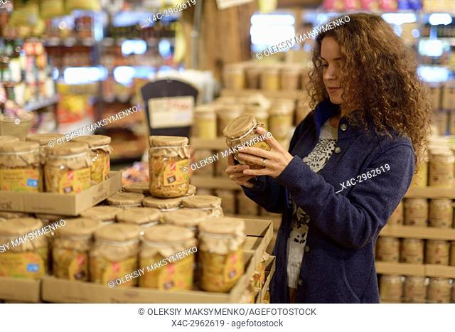Woman at a grocery supermarket store looking at canned food products Canada