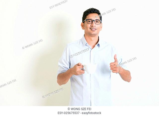 Portrait of handsome casual business Indian male drinking a cup hot coffee and giving thumb up, standing on plain background with shadow, copy space at side