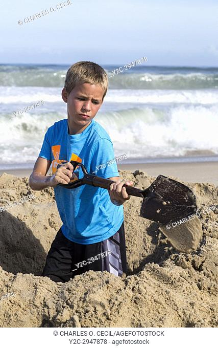 Avon, Outer Banks, North Carolina, USA. Young Boy Digging a Hole in the Sand
