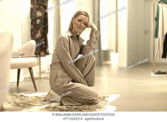 cool fashionable woman kneeling on carpet floor, wearing beige one-piece jumpsuit, in Munich, Germany