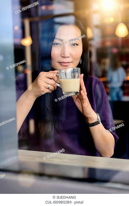 Mid adult woman with coffee looking out from cafe window seat, portrait