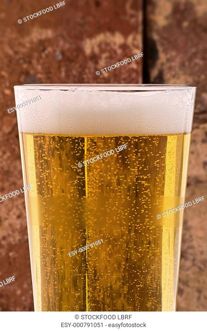 Glass of lager in front of brick wall