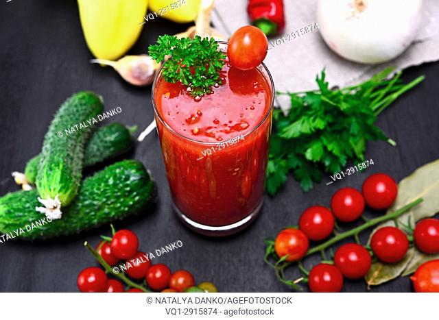 glass of freshly squeezed tomato juice on a table with vegetables, top view