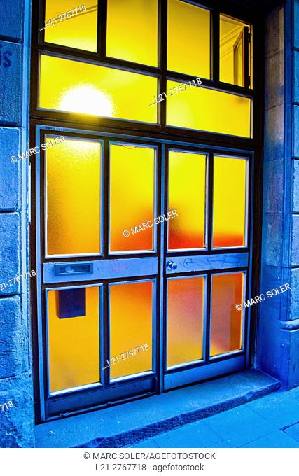 Exterior entrance of a house in a street. Door with transluced glass. Interior with light on. Barcelona, Catalonia, Spain