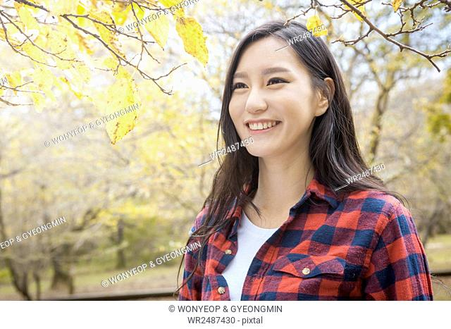 Portrait of young smiling woman in fall