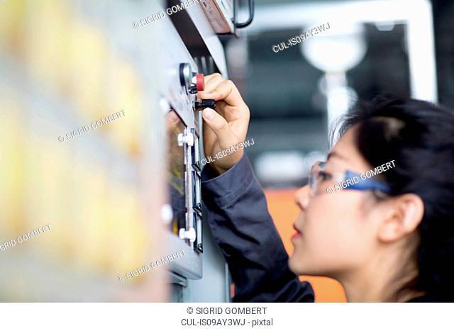 Technician operating machine in factory