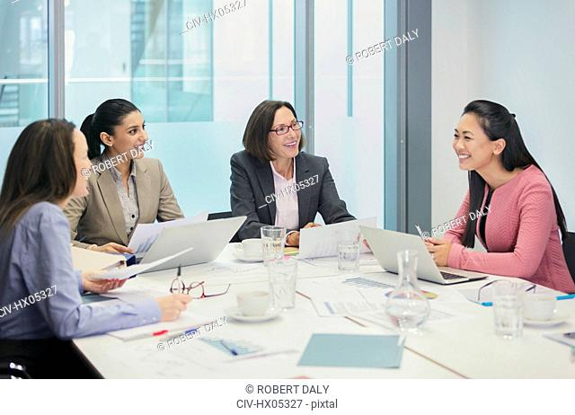 Smiling businesswomen talking in conference room meeting
