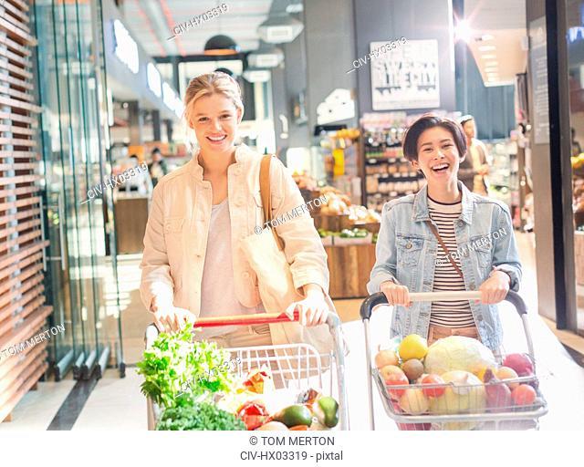 Smiling young women pushing shopping carts in grocery store market
